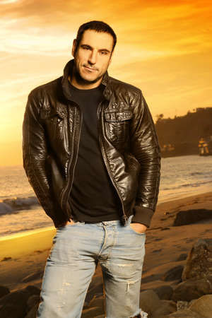 Full body portrait of good looking man in golden light wearing a leather jacket against beautiful sunset