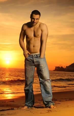 Full body portrait of good looking shirtless man on beach at sunset