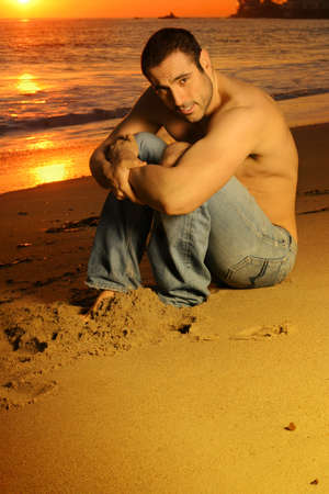 Casual shirtless good looking man on the beach at sunset