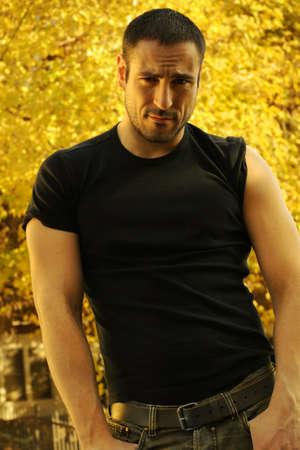 tough: Cuerpo completo de Moody retrato de un hombre atractivo con las mangas arremangadas contra el fondo borroso natural en luz dorada