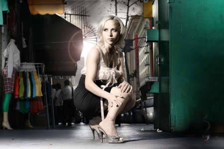 edgy: Dramatic stylized fashion portrait of female model in the city with clothing racks, manequin and flares behind her