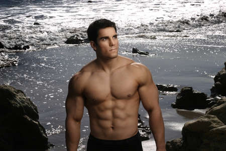 Portrait of a young male bodybuilder against background of sparkling water on beach Stock Photo
