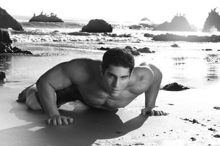 Fine art black and white photo of a young muscular man crawling on beach Stock Photo - 4374058