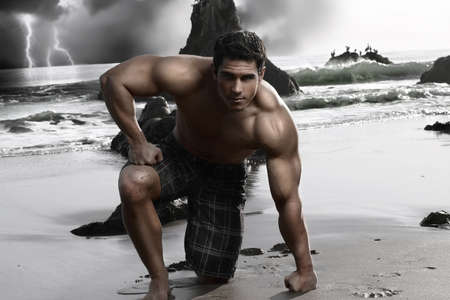 Young muscular shirtless man on the beach with storm and crashing waves in background