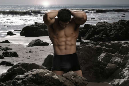 Shirtless bodybuilder flexing muscles on the beach  photo