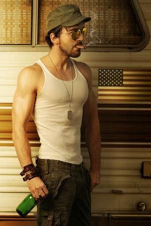 tough: Pareja sexy hombre blanco en mangas y gorra del ej�rcito de fumar cigarros y la celebraci�n de la cerveza en frente de retro remolque