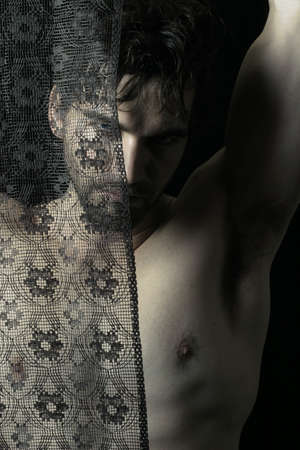 enigma: Portrait of beautiful young shirtless man behind black lace
