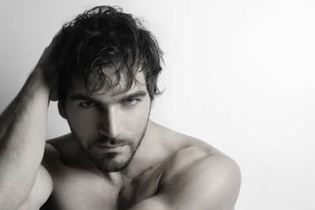 Stylized portrait of masculine attractive young shirtless man with beard against white background photo