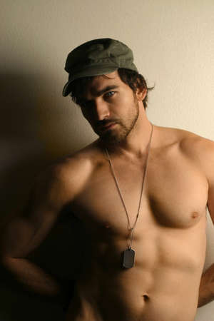 Warm toned portrait of a sexy shirtless military man wearing hat and dog tags photo