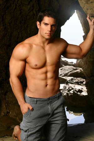 Shirtless young body builder with caves in background