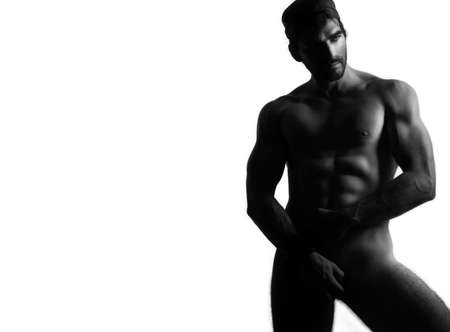 Full body black and white portrait of a sexy nude man against white background