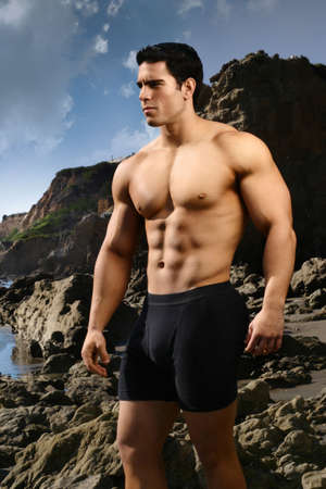 Bodybuilder on the beach with blue sky and rocks behind him photo