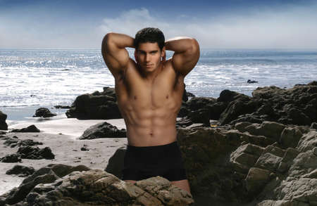 Bodybuilder flexing muscles on the beach with blue sky and ocean photo