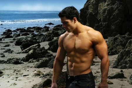 Shirtless bodybuilder op het strand met rotsen en oceaan Stockfoto
