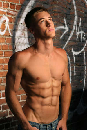 Portrait of a shirtless muscular young man in alley looking up photo