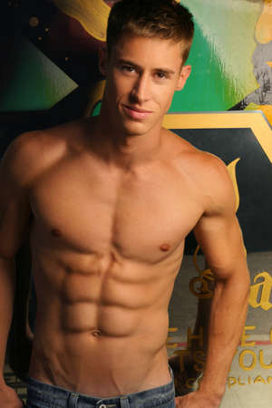 Portrait of a shirtless muscular young man against abstract urban background
