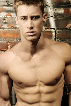 Portrait of a sexy shirtless tough guy against urban brick wall Stock Photo