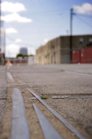 abandoned warehouse: Detail of an empty road with abandoned industrial buildings in background with shallow depth of field