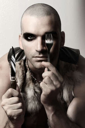 Stylized fashion portrait of extreme looking male model with shaved head and eye makeup holding knife and fork photo