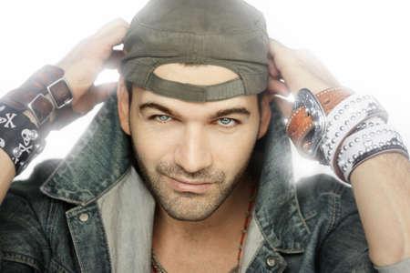 Fashion portrait of male model with bracelet backlit against white background
