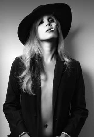 edgy: Glamour fashion shot of sexy female model in black and white smoking