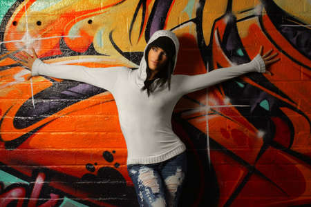 Hip young woman posing against graffiti wall Stock Photo - 6412374