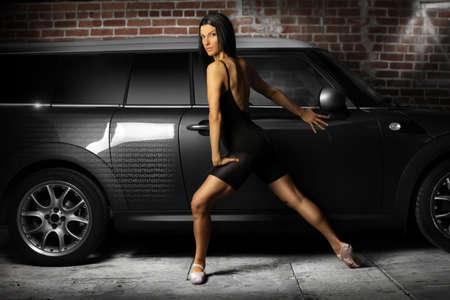 geschniegelt: Hot weiblichen Tanz in Gasse an glatten grauen Auto und Ziegel-Wand