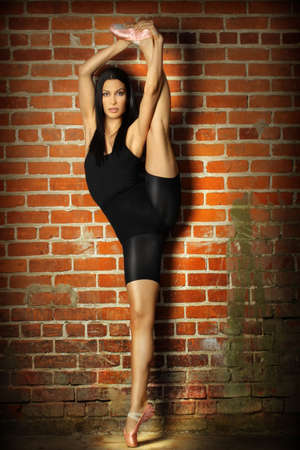 Full body portrait of a flexible beautiful female dancer stretching against brick wall background