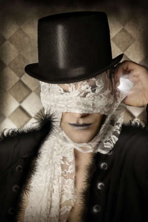 mystique: Fantastical stylized portrait of man in top hat and stylish fur coat with lace covering his face Stock Photo