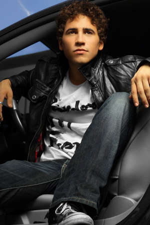 Hip young man in a car wearing leather jacket Stock Photo