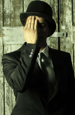 Stylized abstract portrait of a dapper man in top hat and suit covering half of his face with hand photo