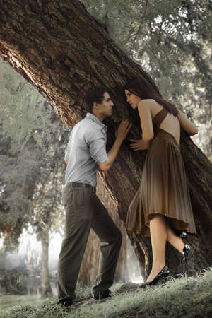 Portrait of young man and woman against tree photo