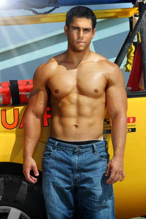 beach hunk: Sexy portrait of a muscular lifeguard on the beach by his truck  Stock Photo