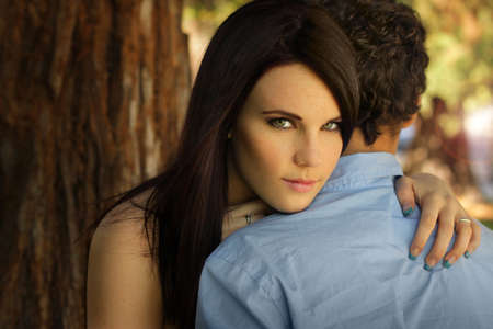 Portrait of beautiful young woman embracing young man in nature setting