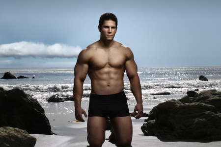 body built: Young fitness model on the beach