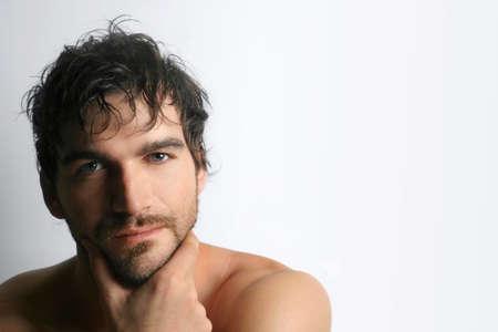 白い背景に対してひげの男性的な魅力的な若い上半身裸男