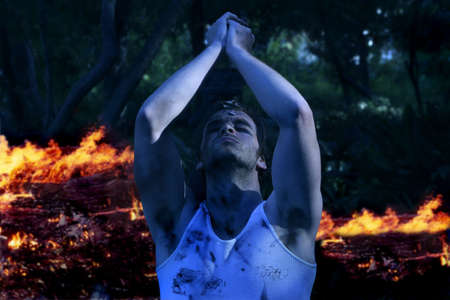 guerrilla warfare: Dramatic portrait of young emotional man with hands up praying in front of fire