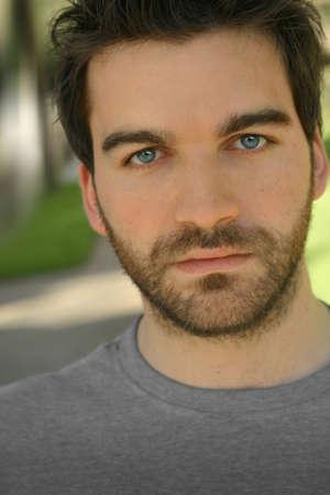 Close-up van outdoor portret van een jonge man gezicht met helder blauwe ogen en baard