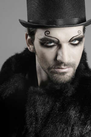 gothic: close-up portrait of young male goth model in face makeup
