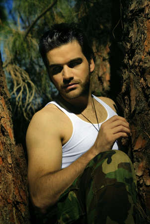 Dramatic stylized portrait of sexy young man in tree