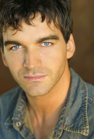 Close-up portrait of young man in denim shirt against brown background photo
