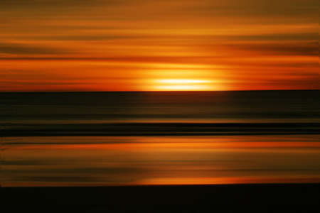 Abstract sunrise or sunset background against blurred ocean photo