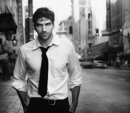 poses de modelos: Vintage foto en blanco y negro estilizado de j�venes modelo masculino contra la calle de la ciudad (Photo tiene un grano de pel�cula intencional)