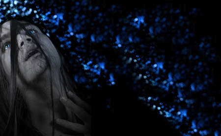 Dramatic portrait of a young long haired man against blue abstract background with lots of copy space photo