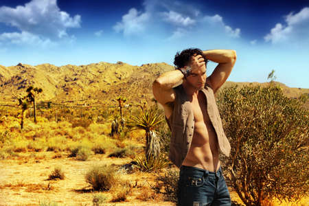 Fashion portrait of a sexy muscular male model in the desert photo