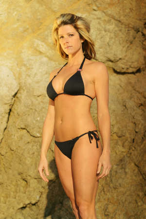 Beautiful female model in black bikini against background of sandstone rocks photo