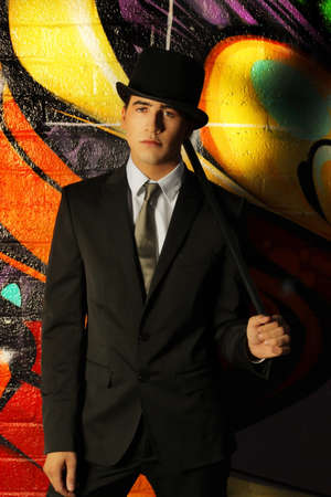 top: Young ma in top hat and cane against abstract background Stock Photo
