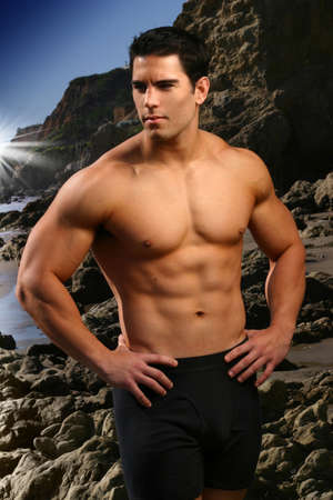 muscular body: Young male fitness model at the beach with rocks and blue sky