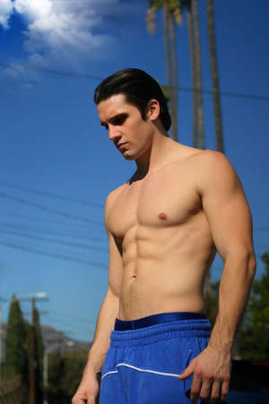 sixpacks: Young muscular male athlete outdoors with blue sky in background Stock Photo
