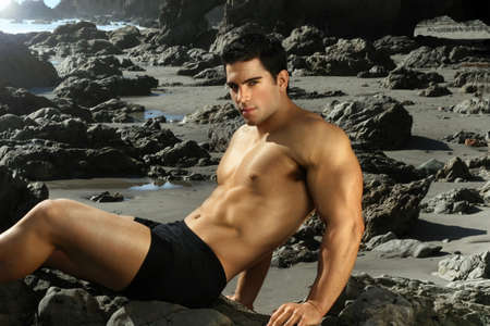 Young male bodybuilder laying on rocky shoreline photo